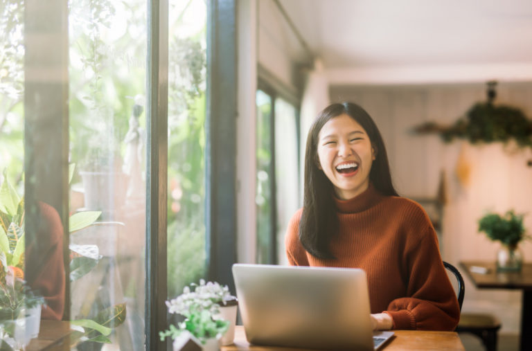 woman laughing while working