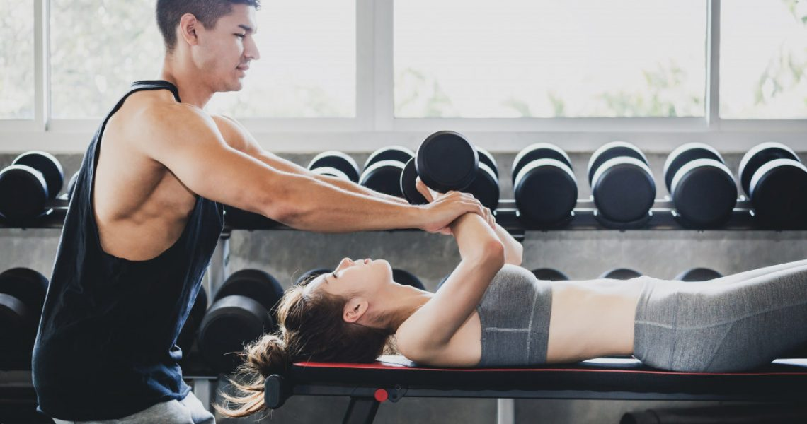 man training woman in the gym
